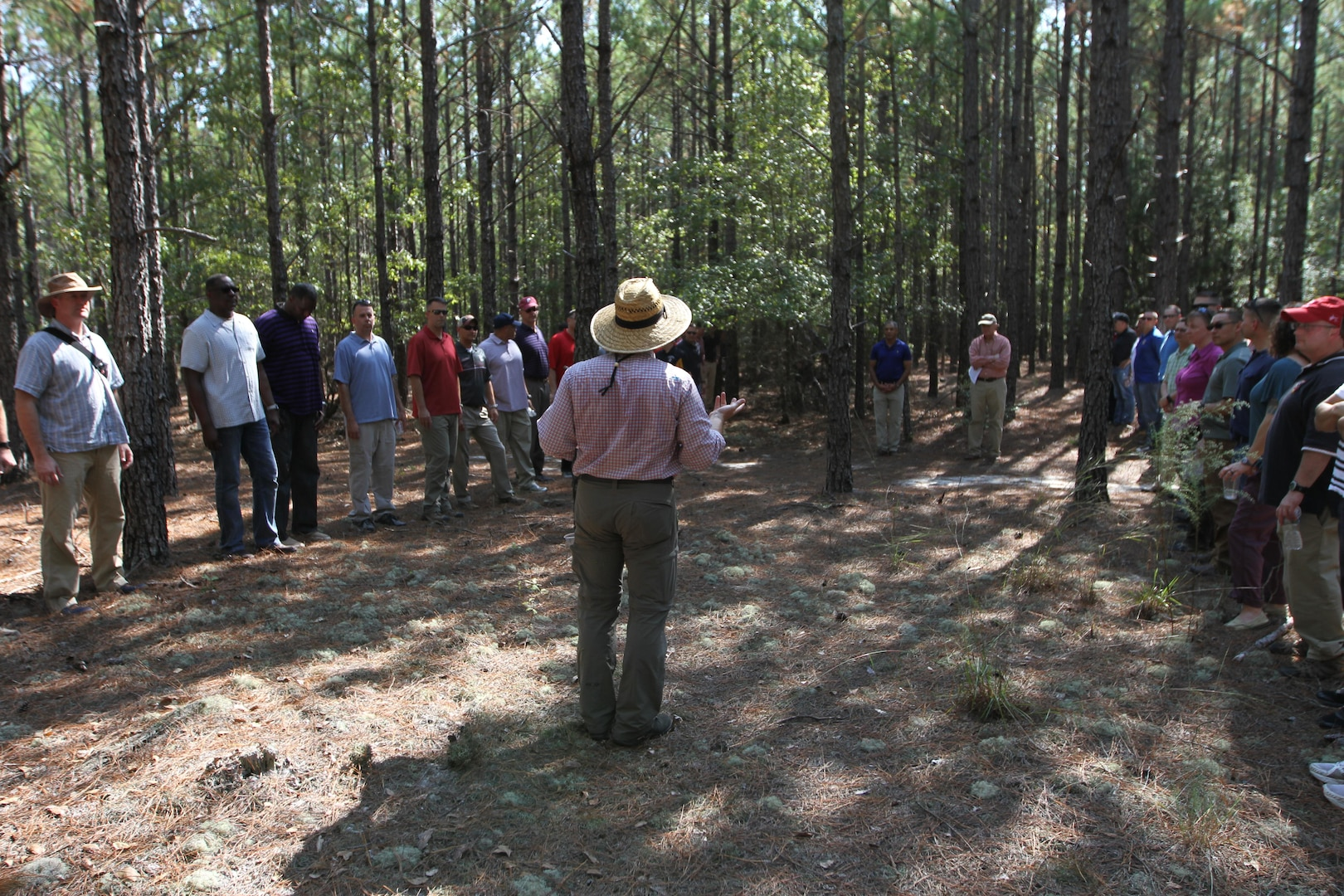 Two groups of people stand facing eachother in the woods while a guide speaks.