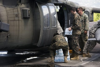 U.S. service members load water into a U.S. Army UH-60 Black Hawk helicopter