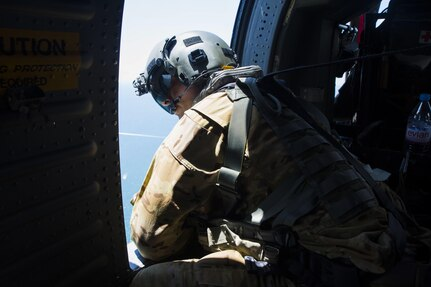 A Soldier looks out of the window of a UH-60 Black Hawk helicopter