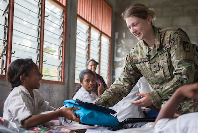 GLENO, Timor Leste (June 15, 2016) Spc. Kayla Sutton, a native of Lake Helen, Florida, assigned to USNS Mercy (T-AH 19), hands out basic hygiene kits to local Timorese children at the Dona Ana Lemos Escuela elementary school during a Pacific Partnership 2016 health outreach event. Service members donated supplies provided by Project Hand Clasp, and educated kids on preventative health measures for basic hand washing, oral hygiene, water safety and mosquito protection. Pacific Partnership 2016 marks the sixth time the mission has visited Timor Leste since its first visit in 2006. Medical, engineering and various other personnel embarked aboard hospital ship Mercy are working side-by-side with partner nation counterparts, exchanging ideas, building best practices and relationships to ensure preparedness should disaster strike. (U.S. Navy photo by Mass Communication Specialist 2nd Class William Cousins/Released)