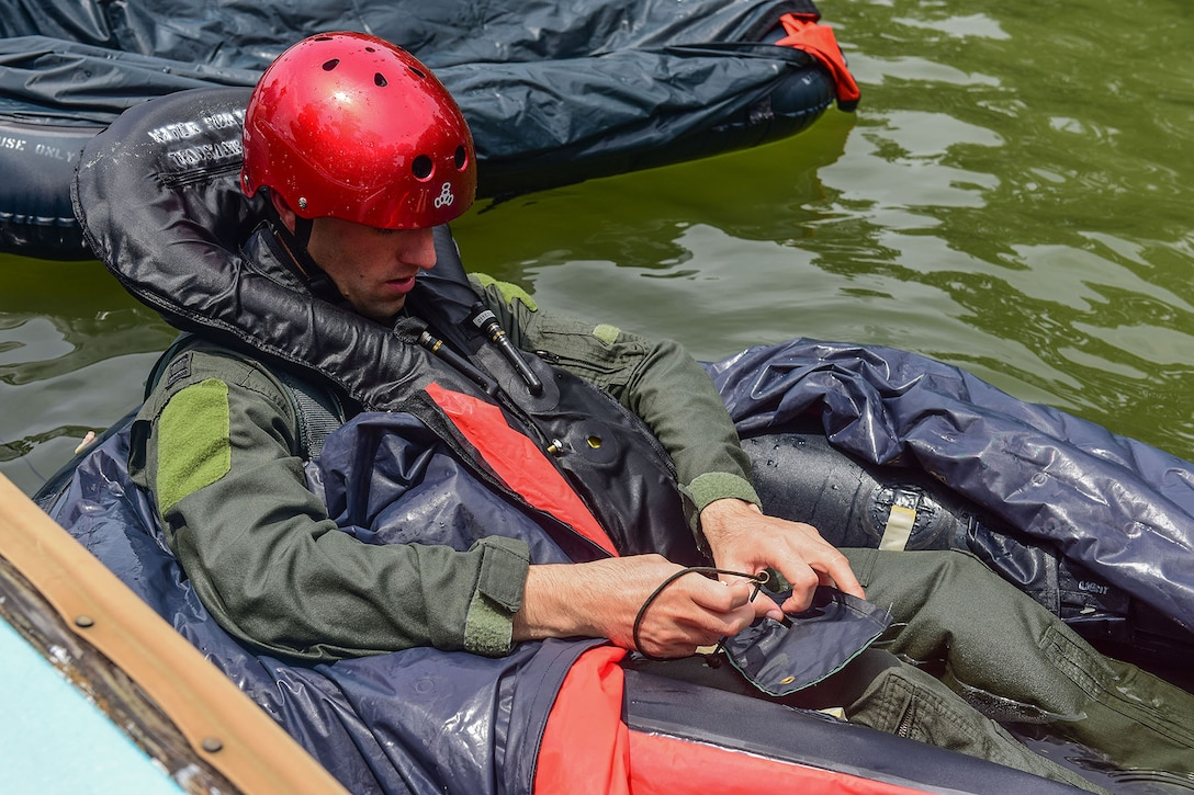U.S. Air Force Capt. Nathan Price, a pilot assigned to the 157th Fighter Squadron, simulates making repairs to a one man life raft during water refresher training conducted in Lake Murray, located in Chapin, S.C., Aug. 13, 2017. The mandatory tri-annual training assesses the pilot's ability to combat scenarios that may take place should they have to eject or bailout of the aircraft over water. (U.S. Air National Guard photo by Senior Airman Megan Floyd)