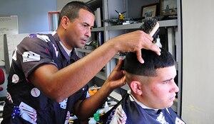 An airman cuts a man's hair.