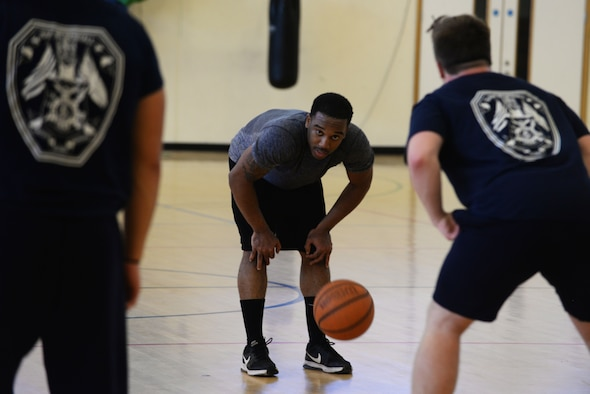 U.S. Air Force Staff Sgt. Jashawn Sherrill, 100th Security Forces Squadron commander's support staff personnelist, plays a game of basketball during the Battle of the Badges Sept. 30, 2017, on RAF Mildenhall, England. Events such as the Battle of the Badges are designed to foster good communication between first responders. (U.S. Air Force photo by Airman 1st Class Alexandria Lee)