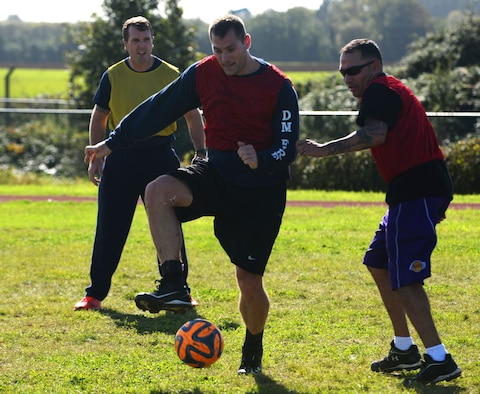 From left, Jamie Greenaway, 100th Civil Engineer Squadron civilian firefighter, U.S. Air Force Staff Sgt. Aaron Scofield and U.S. Air Force Tech Sgt. Andrew Ibarra, 48th Civil Engineer Squadron fire department firefighters play soccer during the Battle of the Badges, Sept. 30,  2017, on RAF Mildenhall, England. The Battle of the Badges was developed as an opportunity for first responders to better develop relationships on and off-base. (U.S. Air Force photo by Airman 1st Class Alexandria Lee)