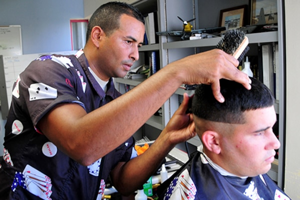 Air Force Senior Airman Roberto Espada-Gali, an aircrew flight equipment technician, cuts hair for members of the 156th Airlift Wing at Muniz Air National Guard base, Puerto Rico, who are helping with recovery efforts after Hurricane Maria. Air Force photo by Senior Master Sgt. Shane A. Cuomo
