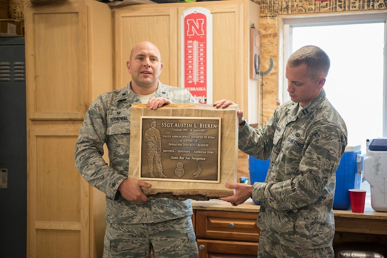 Lt.Col. Chris Fernengel, 4th Space Control Squadron commander (left) and Capt. Brett Stephens, 4th SPCS engineering flight commander current operations presented a plague during the weekly roll call for the 4th SPCS in Elbert, Colo. Sept. 28, 2017. The plaque will hang in the 4th SPCS building so that future squadron members can honor and pay their respects to Bieren. (U.S. Air Force Photo by Steve Kotecki)