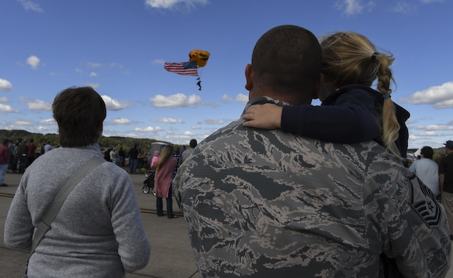 U.S. Air Force Master Sgt. Andy Hill holds his daughter, Elise, while watching as the U.S. Army Golden Knights Parachute Team parachute from the sky Sept. 30, 2017 during the 70th Anniversary Air Show at McLaughlin Air National Guard Base, Charleston, W.Va. 2017 marks the 70th Anniversary of the founding of McLaughlin Air National Guard Base and Yeager Airport which were named in honor of Brig. Gen. James McLaughlin and Brig. Gen. Chuck Yeager, respectfully. (U.S. Air National Guard photo by Airman Caleb Vance)