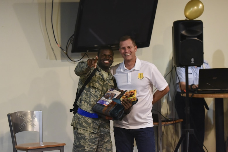 """U.S. Air Force Airman Lanas Jess II, 315th Training Squadron trainee, receives the first place prize from Col. Jeffrey Sorrell, 17th Training Wing vice commander, during the Talent Show at the Crossroads on Goodfellow Air Force Base, Texas, Sept. 29, 2017. Jess played the piano and sang """"Made A Way"""" by Travis Greene. (U.S. Air Force photo by Airman Zachary Chapman/Released)"""