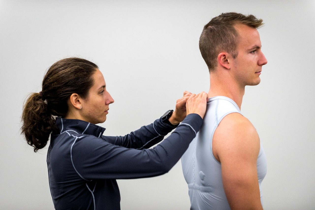 Exercise physiologist Kayla Hierholzer installs a wireless transmitter into base-layer shirt.