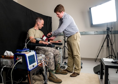 Biomedical engineer Ethan Blackford attaches sensors to test subject Air Force Staff Sgt. Josh Whicker to collect biometric data.