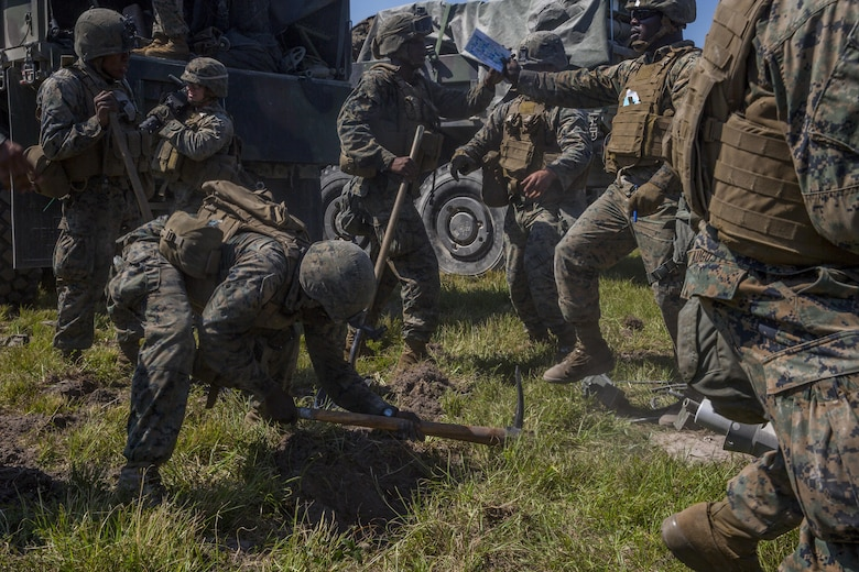 Marines dig holes to emplace an M777 howitzer during a Marine Corps Combat Readiness Evaluation at Camp Lejeune, N.C., Sept. 28, 2017. The Marines conducted the MCCRE to maintain readiness for future operations. The Marines are with 1st Battalion, 10th Marine Regiment. (U.S. Marine Corps photo by Lance Cpl. Taylor W. Cooper)