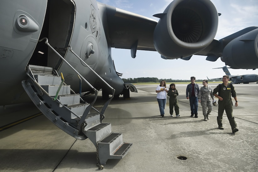 Sandrea Hershey, center left, 14 years old, her mother Lori Hershey, left, and friend Justin Pippin, center, follow Capt. Keane Carpenter, right, 437th Airlift Wing C-17 Globemaster III pilot, to a C-17 as part of an Airman for a Day event here, Oct. 2, 2017. The event was hosted by the 628th Air Base Wing and 437th AW.  Hershey was diagnosed with cancer in 2015 and spent approximately 170 days in a hospital. Despite her diagnosis Hershey kept up with her school work and finished her last treatment last month. Sandrea, her mother and her friend, were also able to meet 628th Security Forces Squadron Phoenix Raven members, observed a military working dog demonstration and test their piloting skills in a C-17 flight simulator. (U.S. Air Force photo by Staff Sgt. Christopher Hubenthal)