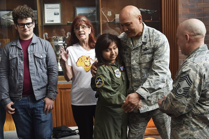 Sandrea Hershey, center left, 14 years old, hugs and thanks Col. Jimmy Canlas, center right, 437th Airlift Wing commander, for hosting her during an Airman for a Day event here, Oct. 2, 2017. The event was hosted by the 628th Air Base Wing and 437th AW.  Hershey was diagnosed with cancer in 2015 and spent approximately 170 days in a hospital. Despite her diagnosis Hershey kept up with her school work and finished her final treatment last month. Sandrea, her mother Lori Hershey, and her friend Justin Pippin, also 14 years old, met 628th Security Forces Squadron Phoenix Raven members, observed a military working dog demonstration, toured a C-17 Globemaster III with Airmen from the 14th Airlift Squadron and tested their piloting skills in a C-17 flight simulator. (U.S. Air Force photo by Staff Sgt. Christopher Hubenthal)
