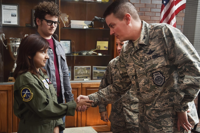 Sandrea Hershey, left, 14 years old, thanks Col. Jeffrey Nelson, right, 628th Air Base Wing commander, for hosting her during an Airman for a Day event here, Oct. 2, 2017. The event was hosted by the 628th ABW and 437th Airlift Wing.  Hershey was diagnosed with cancer in 2015 and spent approximately 170 days in a hospital. Despite her diagnosis Hershey kept up with her school work and finished her final treatment last month. Sandrea, her mother Lori Hershey, and her friend Justin Pippin, also 14 years old, met 628th Security Forces Squadron Phoenix Raven members, observed a military working dog demonstration, toured a C-17 Globemaster III with Airmen from the 14th Airlift Squadron and tested their piloting skills in a C-17 flight simulator. (U.S. Air Force photo by Staff Sgt. Christopher Hubenthal)