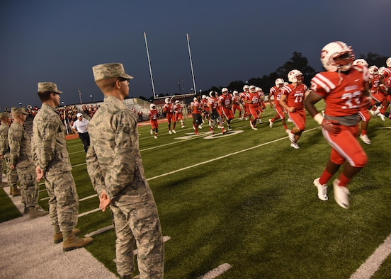 Keesler Airmen line the field during a Biloxi High School military appreciation night football game Sept. 29, 2017, Biloxi, Mississippi. Keesler leadership also participated in the coin toss to determine which team would receive the ball first. (U.S. Air Force photo by Kemberly Groue)