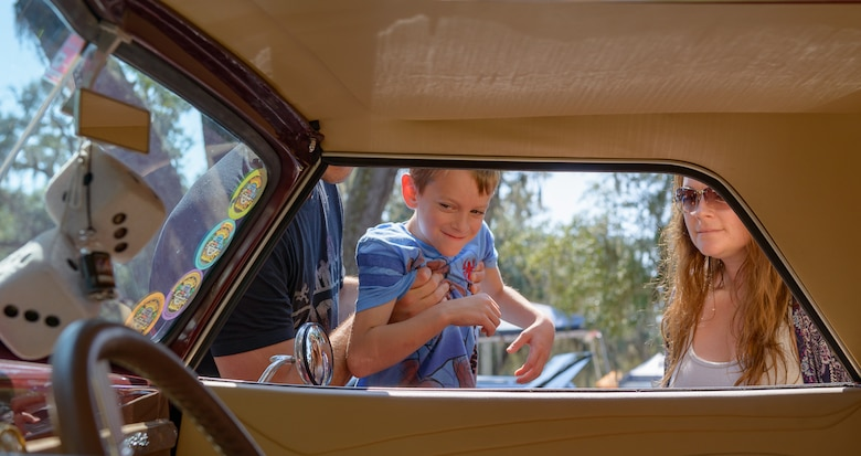 Jaxon Dean, son of Master Sgt. Charles Dean, 81st Medical Support Squadron information flight chief, and his mother, Jessica Dean, look inside of a 1937 Chevy Cabriolet at The Marina Park during the 14th Annual Cruisin' Keesler Car Show Sept. 30, 2017, on Keesler Air Force Base, Mississippi. The annual car show is held to kick off Cruisin' the Coast, a festival to celebrate classic cars, trucks and hot rods, where vehicles cruise down the 30-mile beachside highway in Mississippi. There were over 300 visitors and 130 classic vehicle entries with 15 awards presented. (U.S. Air Force photo by Andre' Askew)