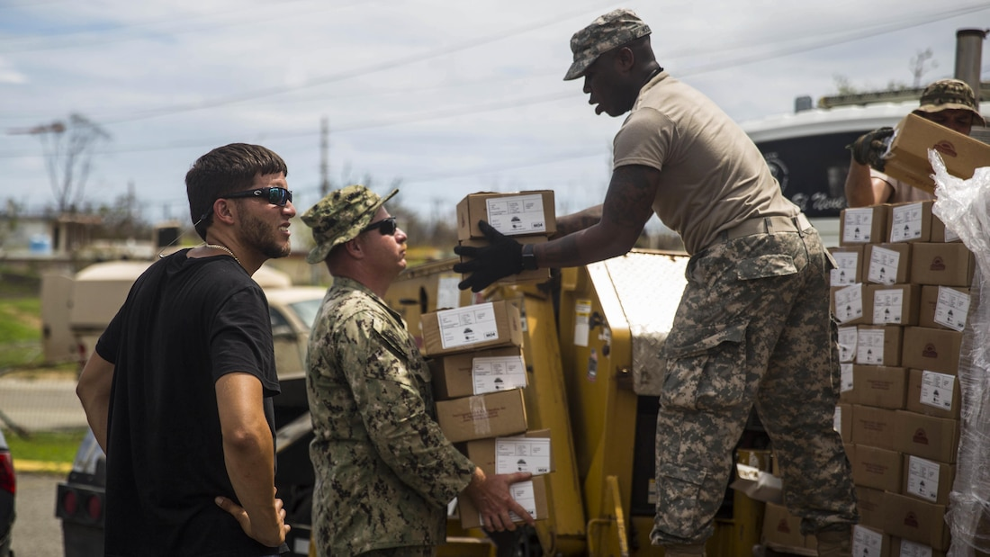 A sailor and soldier unload pallets of relief supplies.