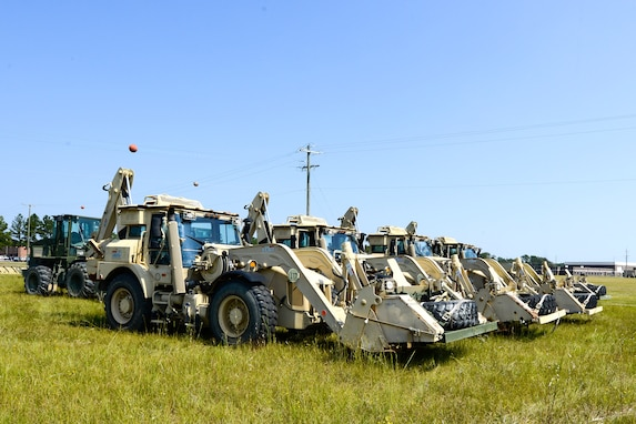 Guardsmen stage bulldozers and backhoes to be transported to Puerto Rico.
