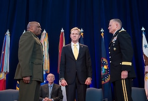 Deputy defense secretary stands between generals.