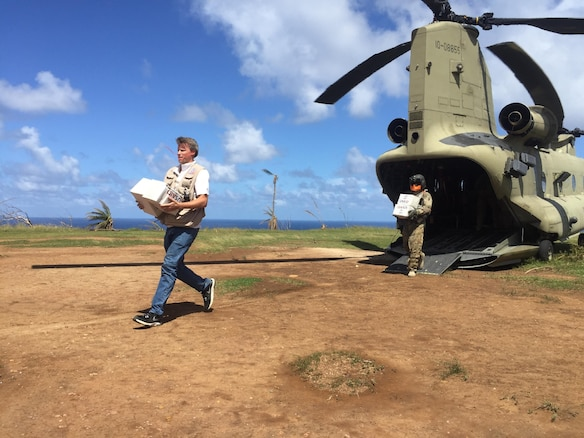 U.S. officials and service members unload aid from helicopter for distribution to the people of Dominica