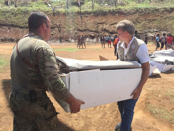 Two people carry a box of supplies from a U.S. Army CH-47 Chinook helicopter at a supply distribution point in Dominica
