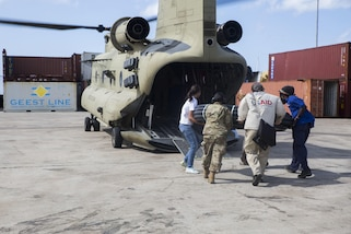 U.S. service members with members of the U.S. Agency for International Development and local citizens load water piping on a U.S. Army CH-47 Chinook helicopter