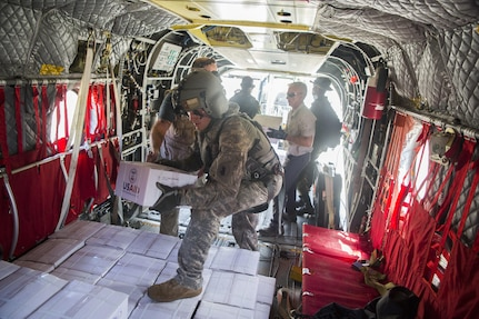 A Soldier helps load kitchen sets on a U.S. Army CH-47 Chinook helicopter at the port of Roseau, Dominica.