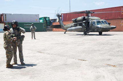 A Soldier coordinates air support for relief operations with the crew of a helicopter in Roseau, Dominica.