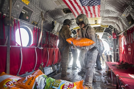 A Soldier helps load rice on a U.S. Army CH-47 Chinook helicopter at the port of Roseau, Dominica.