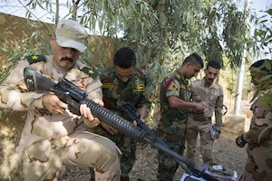 Iraqi security forces trainers disassemble an M16 rifle before they teach their fellow trainers at Camp Taji, Iraq.