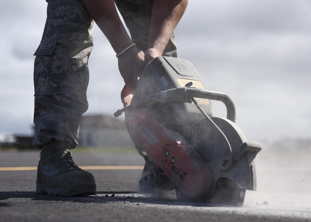 U.S. Air Force Staff Sgt. Trevor Harrison, 633rd Civil Engineer Squadron pavements and construction craftsman, cuts pavement with a power saw at Joint Base Langley-Eustis, Va., Sept. 25, 2017.
