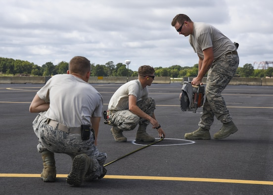 (From Left) U.S. Air Force Airman 1st Class Brandon Whittle, 633rd Civil Engineer Squadron pavements and construction apprentice, Senior Airman Corey Reeves, 633rd CES pavements and construction craftsman, and Staff Sgt. Trevor Harrison, 633rd CES pavements and construction craftsman, prepare to cut the pavement at Joint Base Langley-Eustis, Va., Sept. 25, 2017.