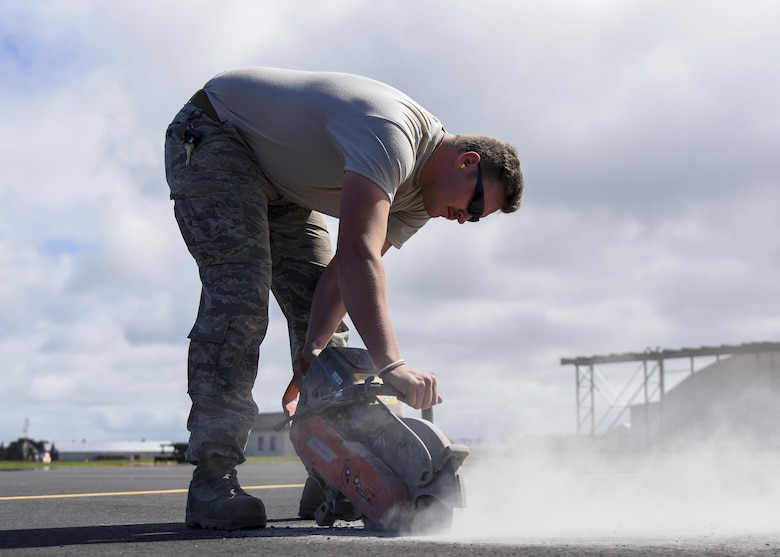 U.S. Air Force Staff Sgt. Trevor Harrison, 633rd Civil Engineer Squadron pavements and construction craftsman cuts the pavement with a power saw at Joint Base Langley-Eustis, Va., Sept. 25, 2017.