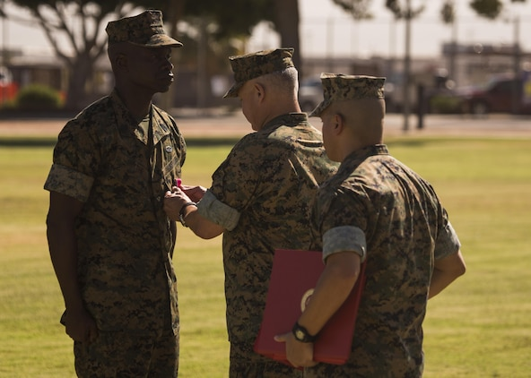 U.S. Marine Corps Sgt. Maj. Delvin R. Smythe, the Marine Corps Air Station (MCAS) Yuma, Ariz., sergeant major, receives awards from Col. Ricardo Martinez, the outgoing commanding officer of MCAS Yuma, and Master Gunnery Sgt. Arthur Parra, the acting sergeant major of MCAS Yuma, during Sgt. Maj. Smythe's retirement ceremony, June 30, 2017. (U.S. Marine Corps photo taken by Lance Cpl. Christian Cachola)