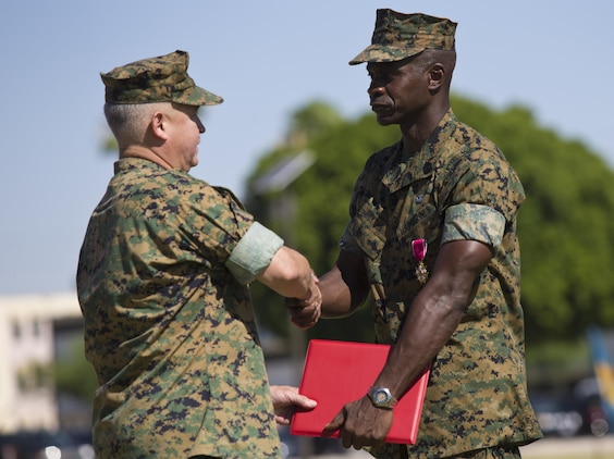U.S. Marine Corps Sgt. Maj. Delvin R. Smythe, the Marine Corps Air Station (MCAS) Yuma, Ariz., sergeant major, receives awards from Col. Ricardo Martinez, the outgoing commanding officer of MCAS Yuma, and Master Gunnery Sgt. Arthur Parra, the acting sergeant major of MCAS Yuma, during Sgt. Maj. Smythe's retirement ceremony, June 30, 2017. (U.S. Marine Corps photo taken by Lance Cpl. Joel Soriano)