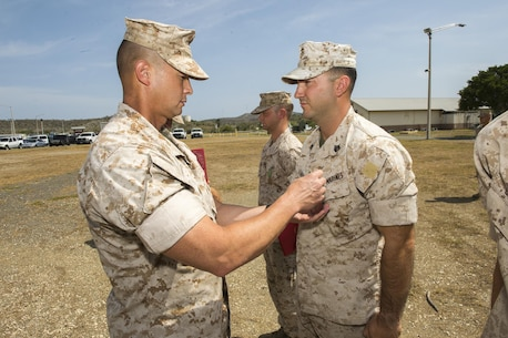 Col. Brian W. Neil, commanding officer, Marine Corps Security Forces Regiment, presents three Marines with the Navy and Marine Corps Achievement Medal during his visit to Marine Corps Security Force Company Guantanamo Bay on Aug. 24., Guantanamo Bay, Cuba. Following the formation, the Marines of Headquarters Company and Charlie 3, Fleet Anti-terrorism Security Team, MCSFR, presented Neil with a flag flown at the Northern gate. (Official Navy photo by Petty Officer 1st Class John P. Wagner Jr./ Released)