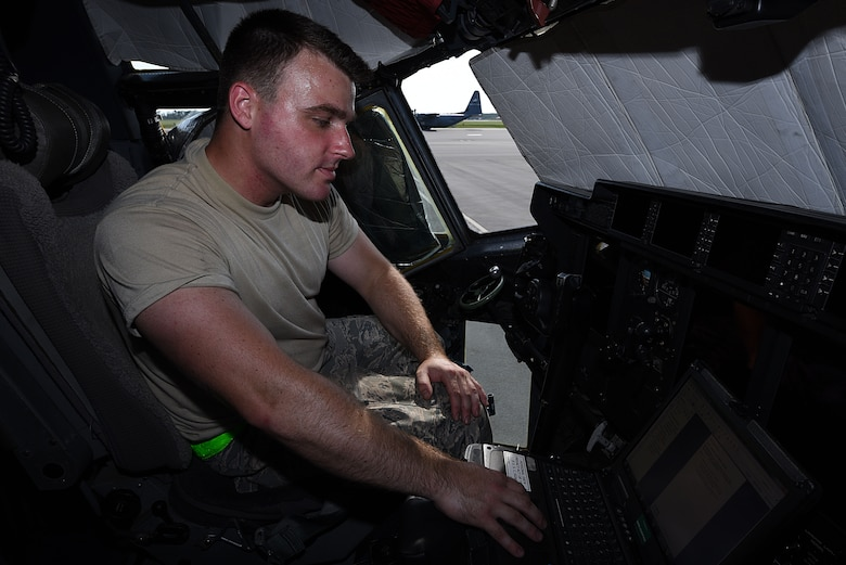 Male sits in flight deck monitoring plane systems