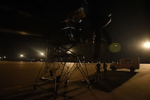Two people on a maintenance stand work on an airplane prop on a flight line at night.