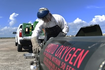 Male monitors liquid oxygen levels while transferring them to a  green portable liquid oxygen unit.