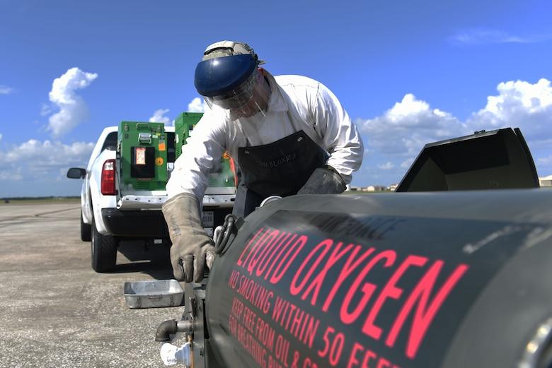 Male monitors liquid oxygen levels while transferring them to a  green portable liquid oxygen unit.