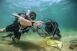 Two divers work with wires underwater.