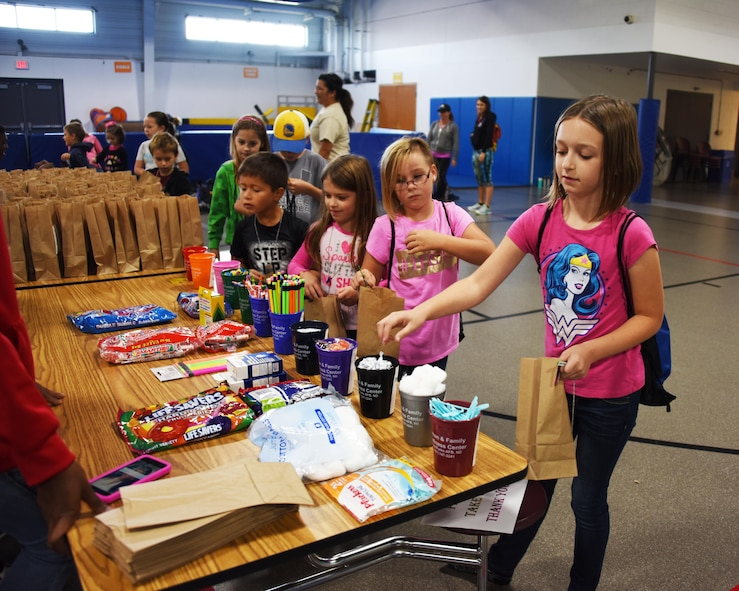 Children from across the base gather goodies for their deployment bag during a kid's deployment day event Sept. 29, 2017, at Grand Forks Air Force Base, North Dakota. The deployment day was sponsored by the Network 5/6 whose goal was to give the kids a feel for what a deployment is like. (U.S. Air Force photo/Senior Airman Cierra Presentado)
