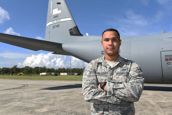 Male Airman stands in front of aircraft tail