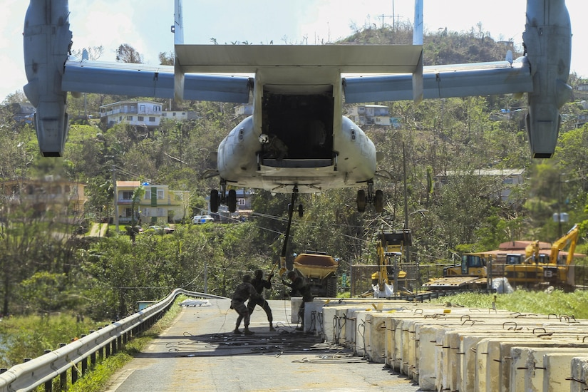 Marines attach a barrier to a V-22 Osprey tilt-rotor aircraft while working to reinforce the Guajataca Dam in Puerto Rico.