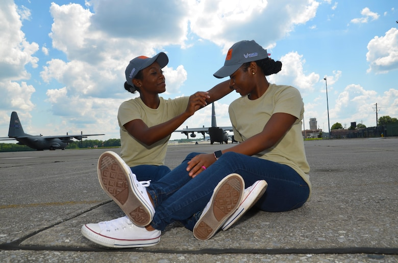 Shaina Williams adjusts Shannon Barber's hat as they pose for a photo on the flightline at Dobbins Air Reserve Base, Ga. July 9, 2017. The sisters are identical twins and currently train with the 94th Airlift Wing development and training flight. (U.S. Air Force photo/Senior Airman Lauren Douglas)