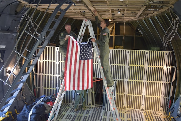 Senior Master Sgt. Kevin Foerster a 68th Airlift Squadron loadmaster and Senior Airmen Antonio Farias a 433rd Aircraft Maintenance Squadron crew chief climb a ladder to affix a United States flag to the ceiling of an Air Force Reserve Command C-5M Sup