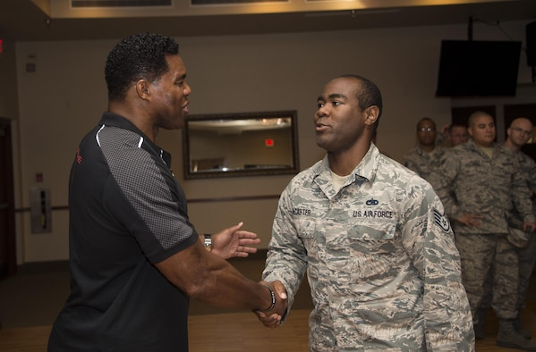 Herschel Walker, former professional athlete, shakes hands with Staff Sgt. Ned McCaster, 62nd Aircraft Maintenance Unit F-35 integrated avionics specialist, at Luke Air Force Base, Ariz., Oct. 3, 2017. Concluding his speech, Walker conducted a meet-and-greet and photo opportunity for all Airmen in attendance. (U.S. Air Force photo/Airman 1st Class Alexander Cook)