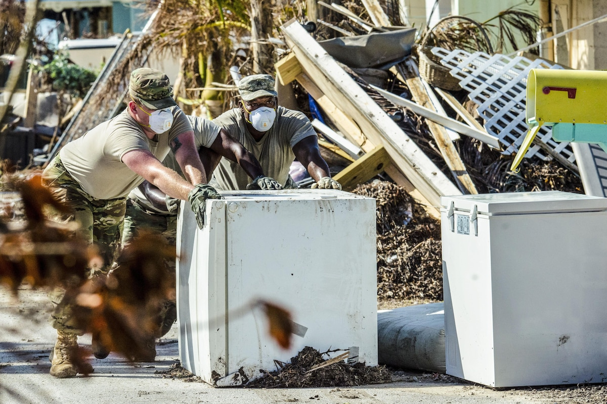 Two soldiers wearing dust masks push a refrigerator outside amid debris.