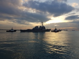 CHANGI, Singapore (NNS) - The Arleigh Burke-class guided missile destroyer USS John S. McCain (DDG 56) is towed away from the pier at Changi Naval Base, Oct. 5, to meet heavy lift transport vessel MV Treasure. Treasure will transport McCain to Fleet Activities Yokosuka for repairs.
