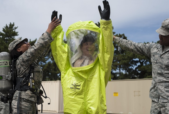 U.S. Air Force Master Sgt. Ambree Evans, 8th Medical Group Bioenvironmental Engineering health operations NCOIC, and Staff Sgt. Adam Ruiz, 8 MDG industrial hygiene NCOIC, help a student from Kunsan National University don protective gear while on tour at Kunsan Air Base, Republic of Korea, Sept. 29, 2017.  During the tour, the environmental engineering students were taught about the correlation between the environment and health and what the 8th MDG is doing to minimize risks to the Airmen and civilians on base. (U.S. Air Force photo by Staff Sgt. Victoria H. Taylor)